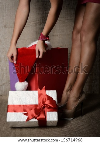 Beautiful young woman with gift box, santa's hat and colored shopping bags, long legs on high heels closeup over canvas background, glamour holiday shopping concept, image toned  - stock photo