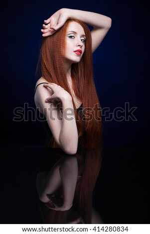 Beautiful young woman with ginger hair  over reflection mirror on blue background