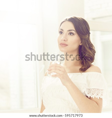 Beautiful, young woman with glass of water. Relaxing at home.