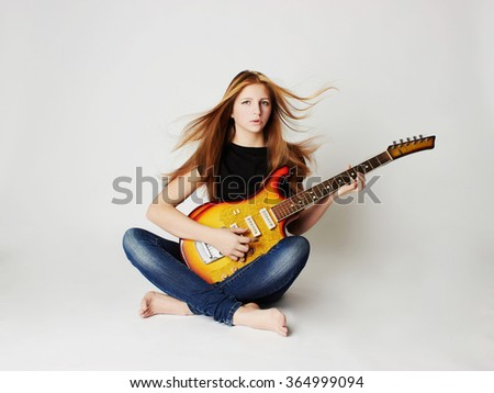 beautiful young woman with guitar.sexy girl in jeans.rock music - stock photo