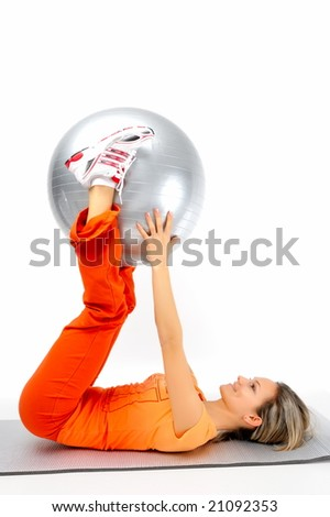 beautiful young woman with gym ball exercising - stock photo