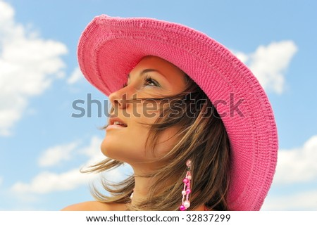 beautiful young woman with hat on the beach