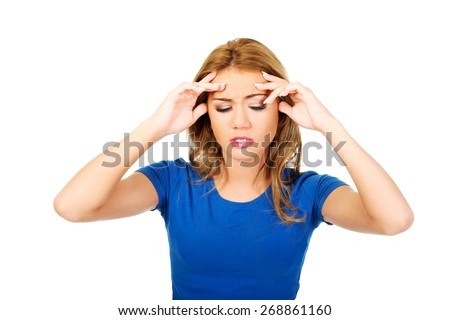 Beautiful young woman with headache touching her head. - stock photo