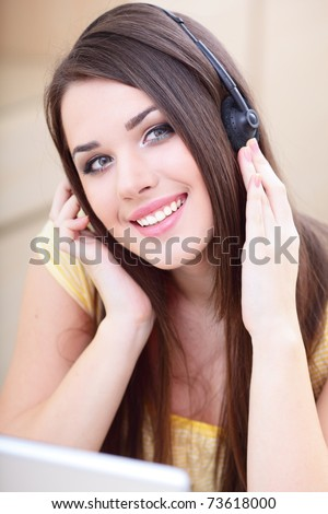 Beautiful young woman with headphones and laptop at home - stock photo