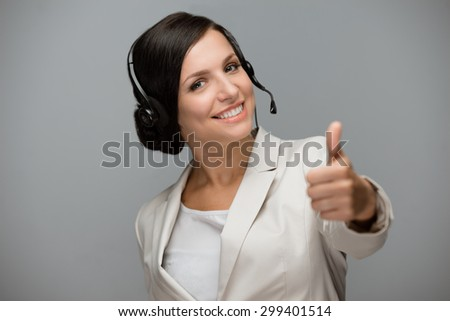 Beautiful young woman with headphones looking at camera at call center and showing thumb up. Grey background - stock photo