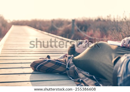 Beautiful Young Woman with Headphones lying on a catwalk at Outdoors - stock photo