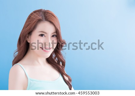 Beautiful young woman with health teeth and charming smile. Isolated over blue background, asian beauty