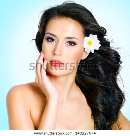 Beautiful young woman with healthy clean skin of face with flowers - stock photo