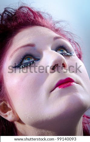 Beautiful young woman with heavy makeup looking up