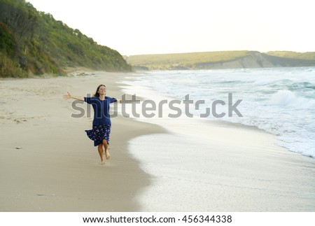 Beautiful young woman with her arms up running on and enjoying the sense of freedom on a desolate beach. - stock photo