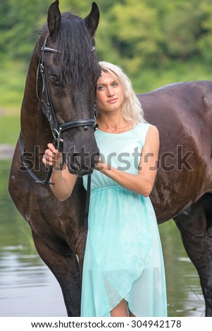 Beautiful young woman with her black stallion. - stock photo