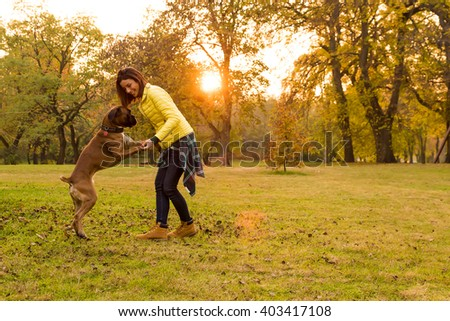 Beautiful young woman with her Dog in the Park in the autumn. - stock photo