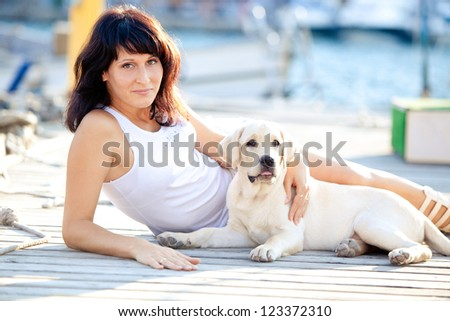 Beautiful young woman with her dog on a summer day sitting at the beach - stock photo