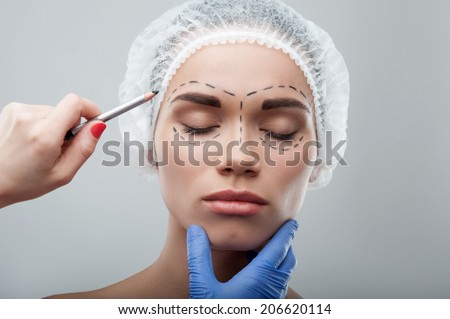 Beautiful young woman with her eyes shut, in surgical cap with perforation lines on her face before plastic surgery operation. Beautician drawing lines on face. Isolated on grey - stock photo