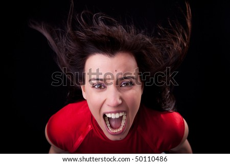 beautiful young woman with her hair in the wind, screaming in fury - stock photo