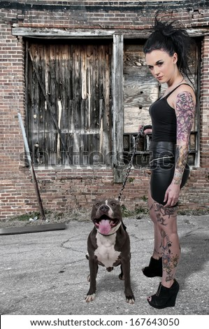 Beautiful young woman with her pit bull dog - stock photo