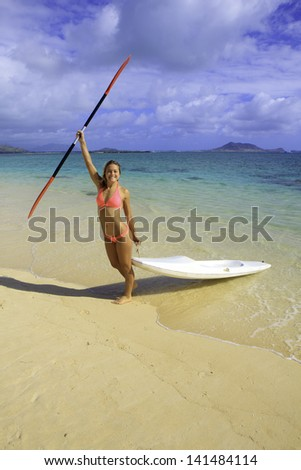 beautiful young woman with her surf ski - stock photo