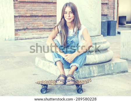 beautiful young woman with his spotted skateboard - stock photo