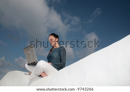beautiful young woman with laptop computer surfing the web relaxing outdoors