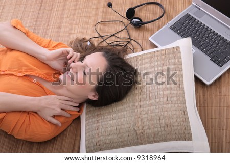 beautiful young woman with laptop talking on the cell phone - stock photo