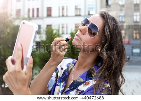 Beautiful young woman with lipstick / photography of brunette girl with pink colored lipstick looking at smartphone.