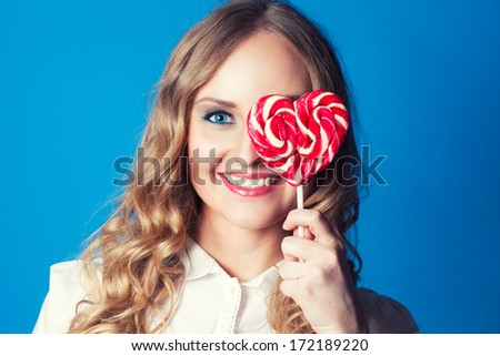 Beautiful young woman with lollipop on blue background - stock photo