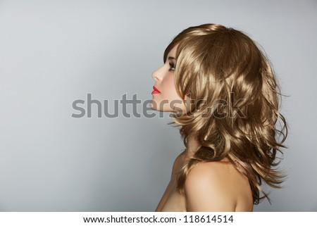 beautiful young woman with long blond curly hair  on studio background with space for text - stock photo
