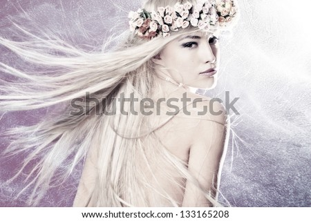 beautiful young woman with long blond flying hair and wreath of flowers - stock photo