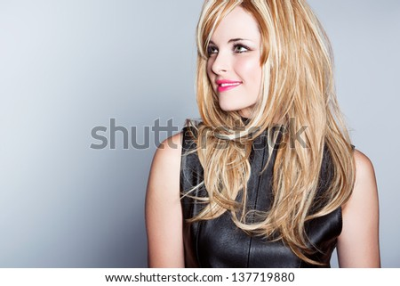 beautiful young woman with long blond hair wearing leather top on studio background with space for text - stock photo