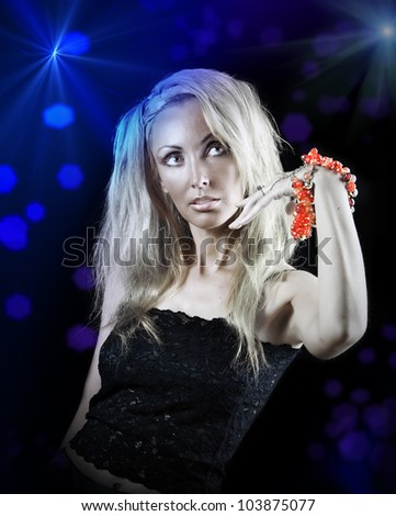 beautiful young woman with long  blonde hair and a red bracelet on a dark background