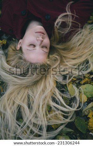 beautiful young woman with long blonde hair sleeping outdoor.
