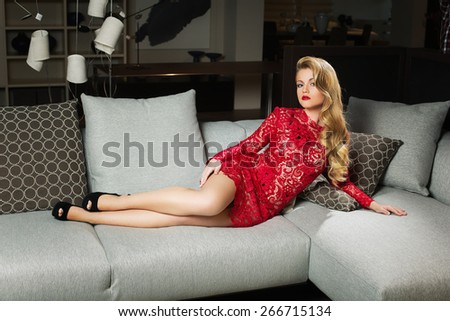 Beautiful young woman with long blonde hair wearing red short lacy dress lying on grey sofa - stock photo