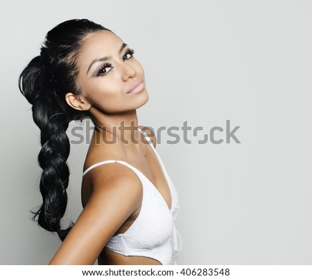 Beautiful young woman with long braided dark hair - stock photo