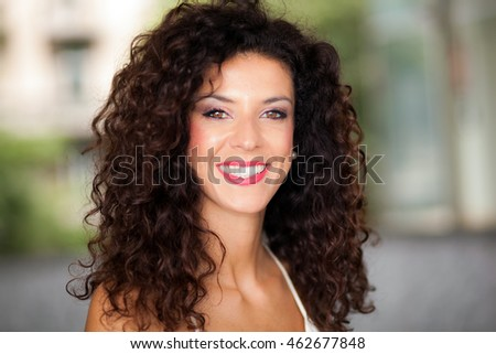 Beautiful young woman with long brown curly hair