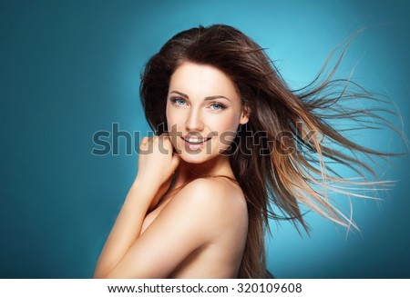 Beautiful young woman with long brown flying hair on  blue backg - stock photo