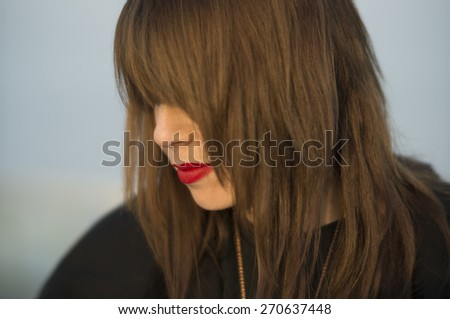 Beautiful young woman with long brown hair and red lipstick on a sunny winter day. - stock photo
