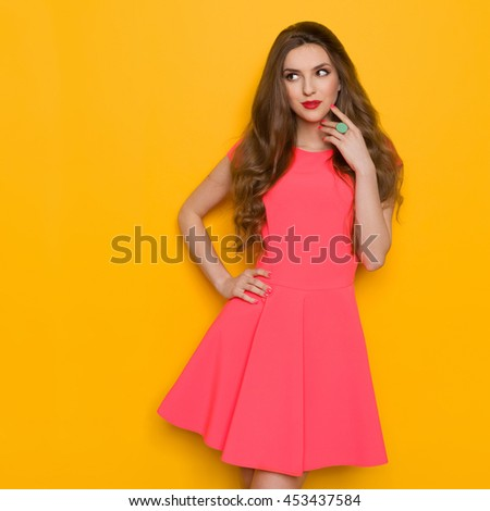 Beautiful young woman with long brown hair in pink mini dress posing with hand on hip, looking away, and thinking. Three quarter length studio shot on yellow background. - stock photo