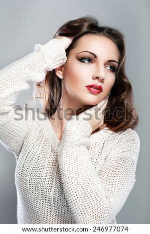 Beautiful young woman with long brown hair. Pretty model poses at studio - stock photo