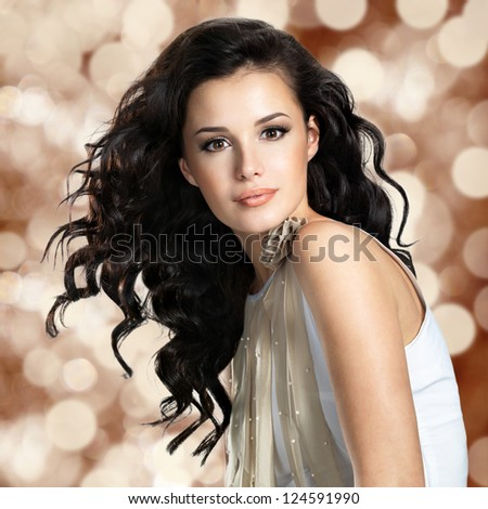 Beautiful young woman with long brown hair. Pretty model poses at studio. Blinking Background. Bokeh - stock photo