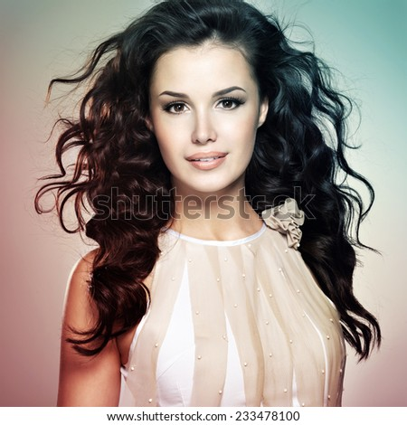 Beautiful young woman with long brown hair. Pretty model poses at studio. Concept image is in tinting colorize style - stock photo