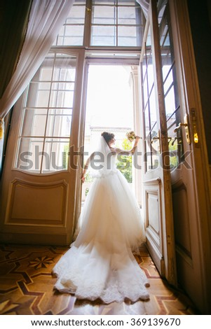 Beautiful young woman with long curly hair posing in white wedding dress in luxury palace. Attractive bride. on balkoi - stock photo