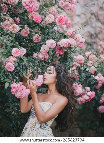 Beautiful young woman with long curly hair posing near roses in a garden - stock photo