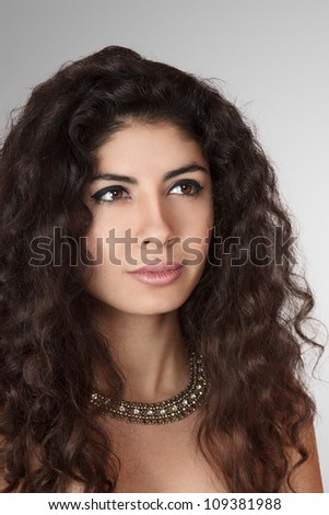 Beautiful young woman with long curly hair studio portrait - stock photo
