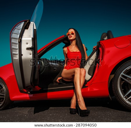 beautiful young woman with long dark hair in red bodysuit and sunglasses sitting in red cabrio - stock photo