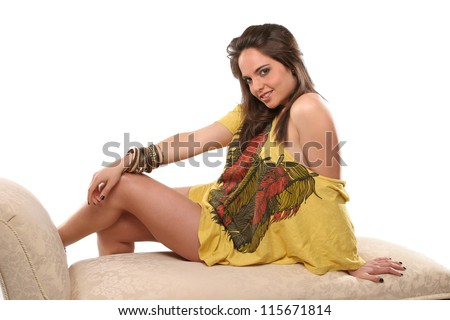 Beautiful young woman with long dark hair smiling sitting on a sofa