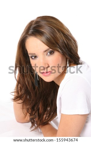Beautiful young woman with long dark hair wearing a white t shirt on a white background - stock photo