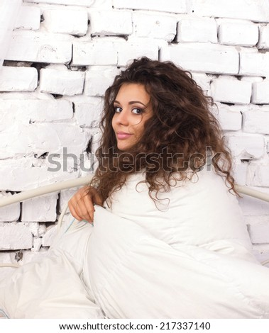 beautiful  young woman with long dishevelled curls sitting  under duvet on white bricky wall background - stock photo