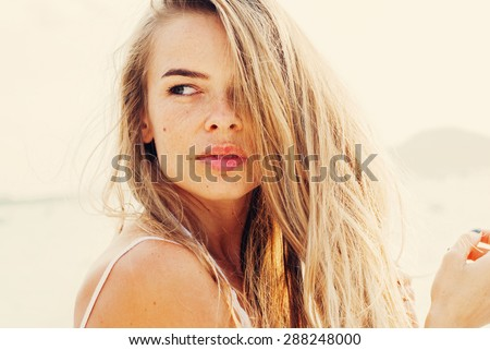 Beautiful Young Woman with Long Fair Hair, Looking to the Right. Toned Effect - stock photo