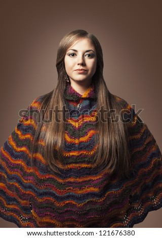 beautiful young woman with long hair and poncho looking at camera - stock photo