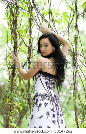 Beautiful young woman with long hair in foliage - stock photo